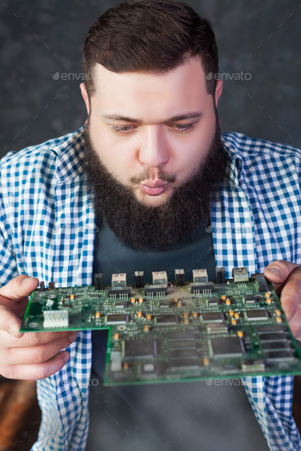 Male engineer blows off the dust from motherboard - Stock Photo - Images