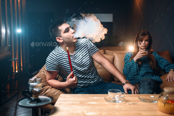 Young couple relax and smoking hookah - Stock Photo - Images