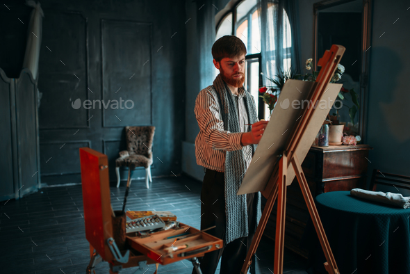 Male painter with brush in front of easel - Stock Photo - Images