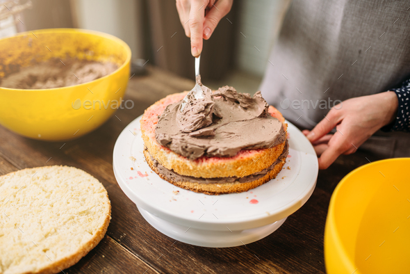 Female hands smears cake with cream closeup view - Stock Photo - Images