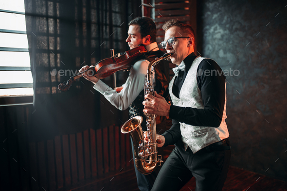 Sax man and fiddler duet playing classical melody - Stock Photo - Images