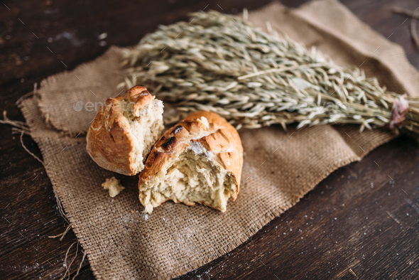 Bread loaf breaked in half, wheat on burlap cloth - Stock Photo - Images