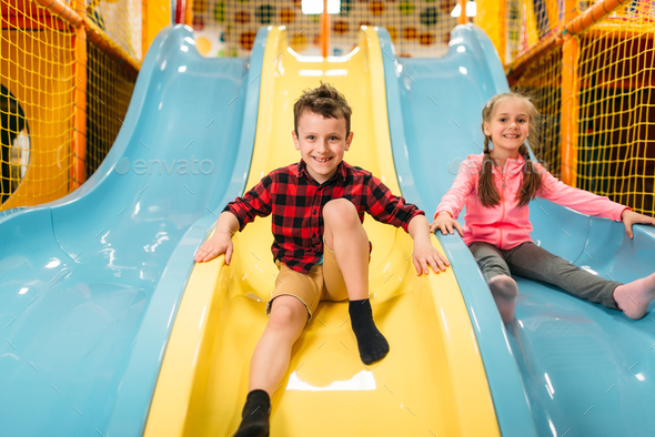 Kids riding from childrens slides in game center - Stock Photo - Images