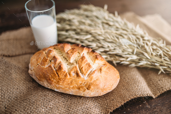Bread, wheat and glass of milk, burlap background - Stock Photo - Images