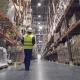 Warehouse Worker Walks Through Rows of Warehouse