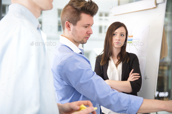 Businesswoman With Arms Crossed Looking At Confident Male Collea - Stock Photo - Images