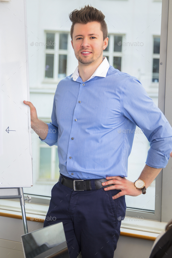 Businessman Standing With Hand On Hip By Flipchart - Stock Photo - Images