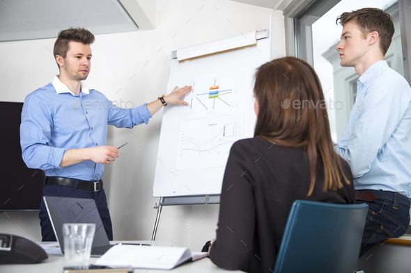 Businessman Explaining Chart To Male And Female Colleagues - Stock Photo - Images