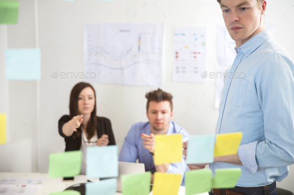 Businessman Looking At Adhesive Notes While Colleagues Pointing - Stock Photo - Images