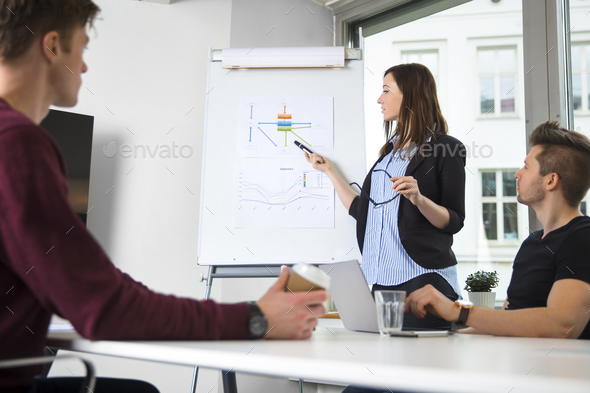 Female Professional Explaining Graph To Male Colleagues - Stock Photo - Images