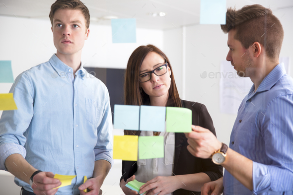 Business People Discussing Over Adhesive Notes Stuck On Glass - Stock Photo - Images