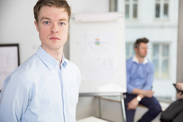 Confident Young Businessman Standing In Office - Stock Photo - Images