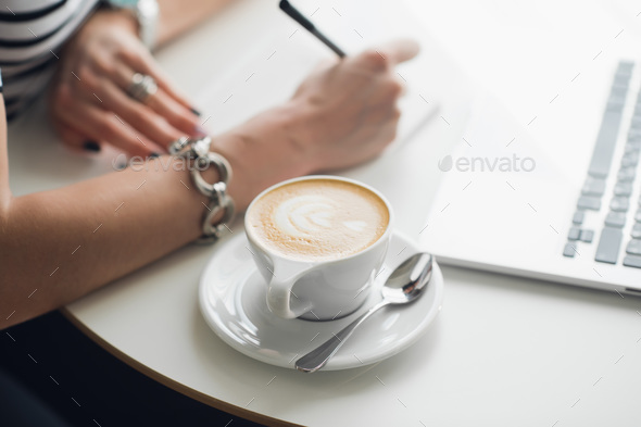 Hot art Latte Coffee in a cup on wooden table and Coffee shop blur background with woman's hands. - Stock Photo - Images