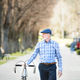 Senior man in blue checked shirt with bicycle in town. - PhotoDune Item for Sale