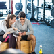 Fit couple in modern crossfit gym with smartphone. - PhotoDune Item for Sale