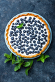 Delicious dessert blueberry tart with fresh berries and whipped cream