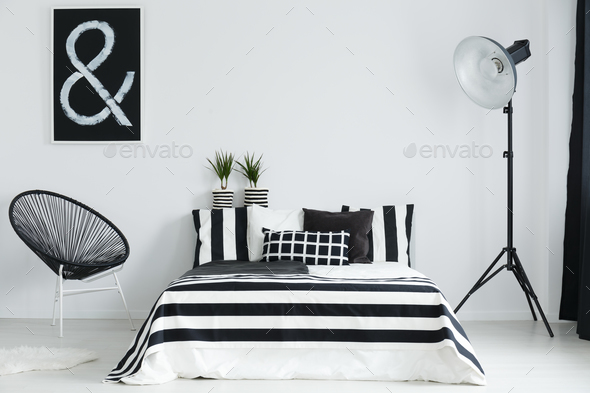 Bedroom with bed, lamp, and chair - Stock Photo - Images