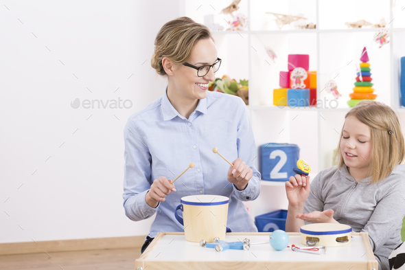 Playing toy instruments with teacher - Stock Photo - Images