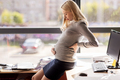 pregnant businesswoman ouching her back at office