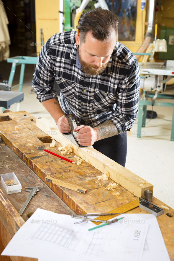 Above view of carpenter work with plane on wood plank in workshop - Stock Photo - Images