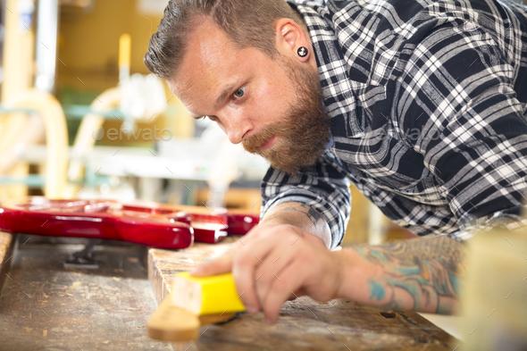 Carpenter sanding guitar neck in wood at workshop - Stock Photo - Images