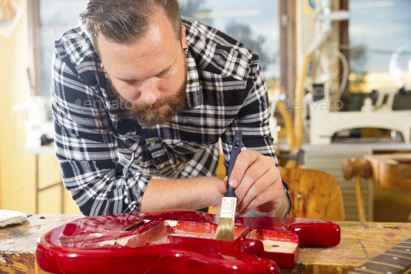 Craftsman with beard working at workshop with a guitar restoration - Stock Photo - Images