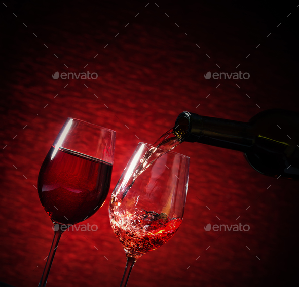 Wine pouring into a glass on red background - Stock Photo - Images