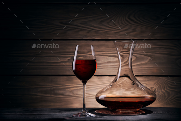 Decanter and glass with red wine on a wooden table - Stock Photo - Images
