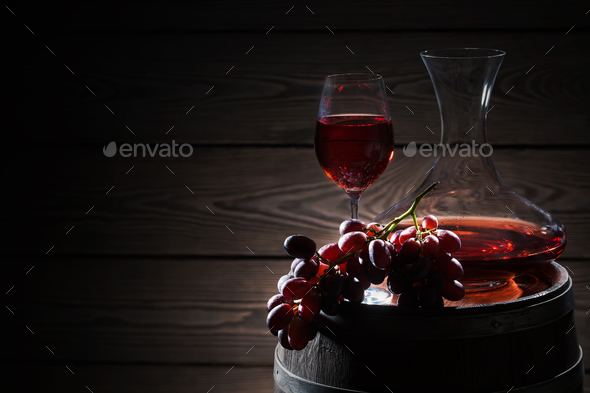 Red wine and a bunch of grapes on barrel - Stock Photo - Images