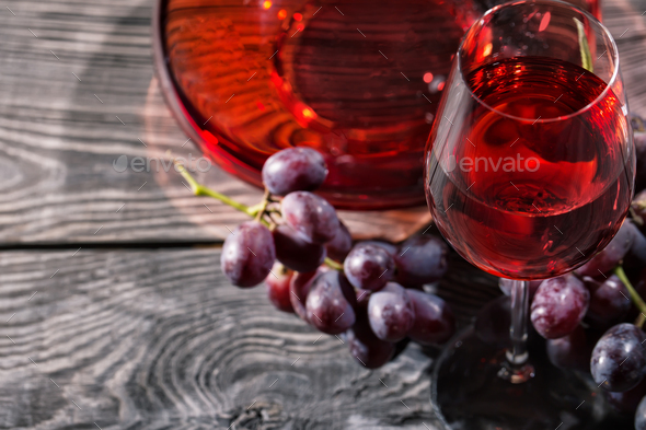 Wooden background with glass of red wine and a bunch of grapes - Stock Photo - Images