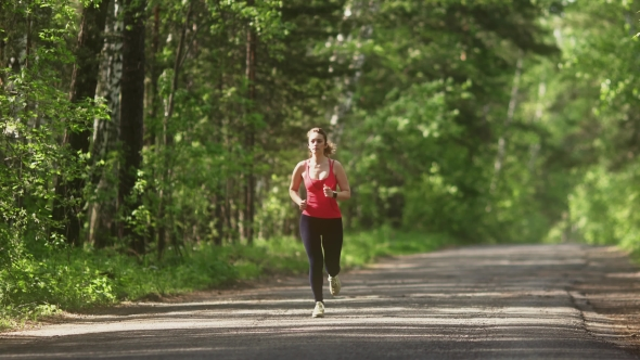 Young Woman Jogging in Summer Forest. the Girl Goes Sports in the Nature
