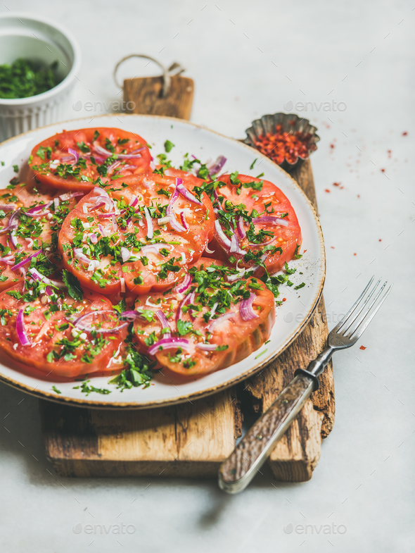Fresh heirloom tomato, parsley and onion salad on wooden board - Stock Photo - Images