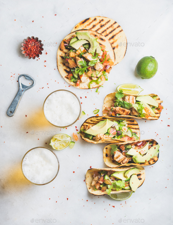 Healthy corn tortillas with chicken, vegetables, limes, beer in glasses - Stock Photo - Images