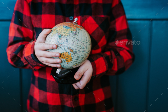 A little boy is holding a globe - Stock Photo - Images