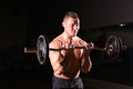Sporty man doing exercises with barbell on dark background