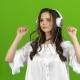 Brunette Listens Through the Headphones with Energetic Music and Builds Grimaces. Green Screen