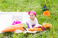 Cute little happy baby girl with big brown teddy bear on green grass meadow, spring or summer season