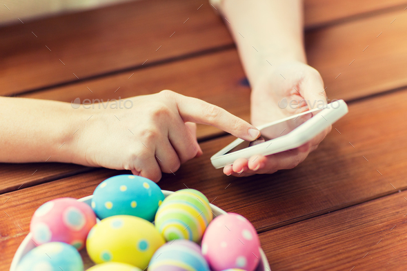 close up of hands with easter eggs and smartphone - Stock Photo - Images