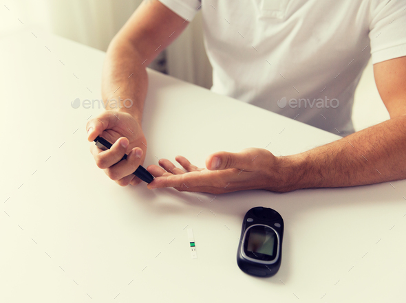 close up of man checking blood sugar by glucometer - Stock Photo - Images