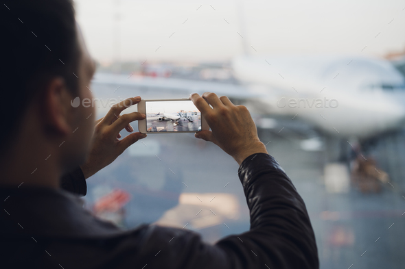 Man hand take picture of airplane using cellphone. Tourism concept photo - Stock Photo - Images
