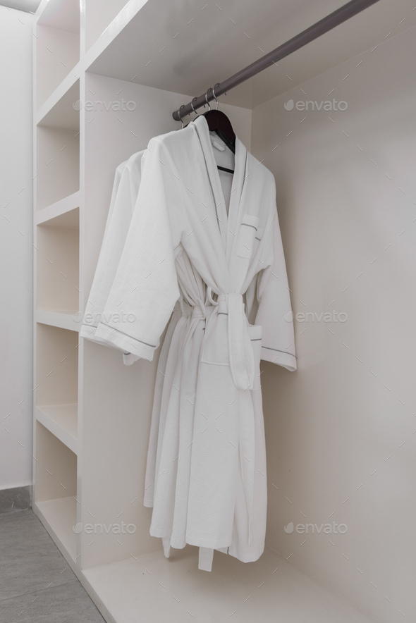 white bathrobe with wooden hangers in wardrobe - Stock Photo - Images