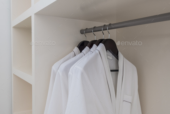 white robes with wooden hangers at dressroom. - Stock Photo - Images