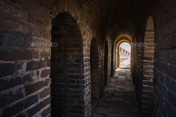 long stone corridor with stairway in ancient castle or wall - Stock Photo - Images