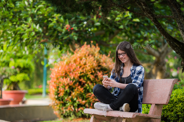 Teenage girl sitting on bench using phone and looking upset - Stock Photo - Images