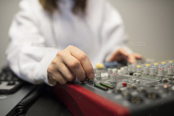 Midsection Of Radio Host's Hand Using Music Mixer In Studio - Stock Photo - Images