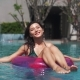 Pretty Girl with Pink Ring Buoy in Swimming Pool