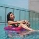 Pretty Girl Resting in Ring Buoy in Swimming Pool