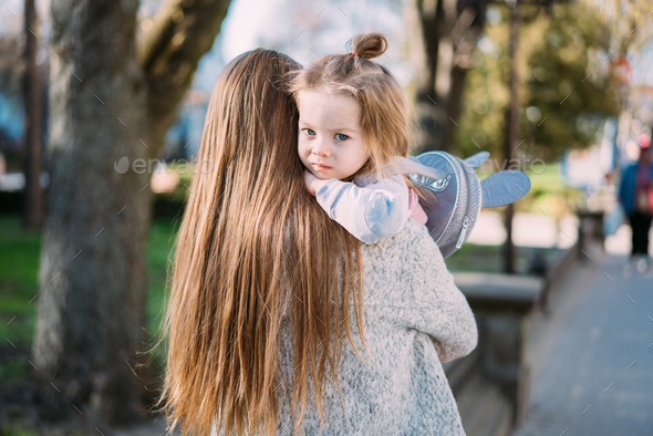 Mother holds a small daughter in her arms - Stock Photo - Images