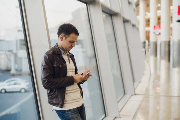 Young business man in airport using smartphone . - Stock Photo - Images