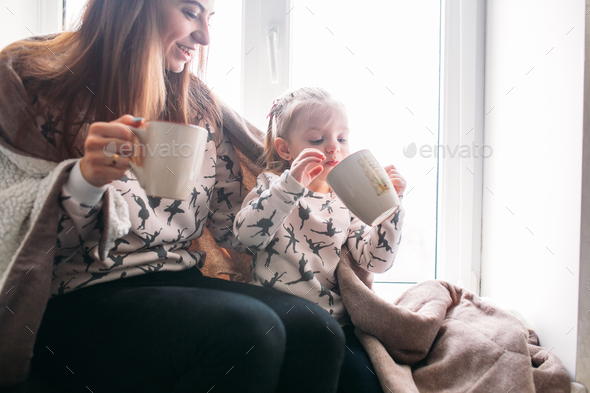 Mom and daughter drink something with mug - Stock Photo - Images